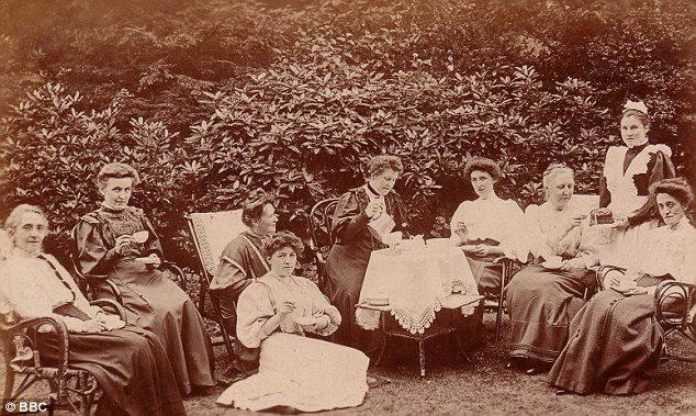 Женщины отдыхают в чайном саду короля Эдуарда в Великобритании, в то время как их обслуживает горничная (вторая справа)