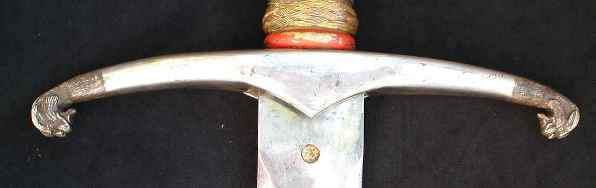 Гарда выполнена из позолоченного серебра, ее кончики выполнены в виде стилизованных голов леопардов