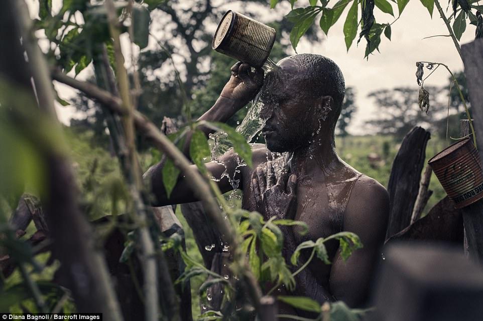Демба Мане обливается святой водой, содержащую несколько видов трав