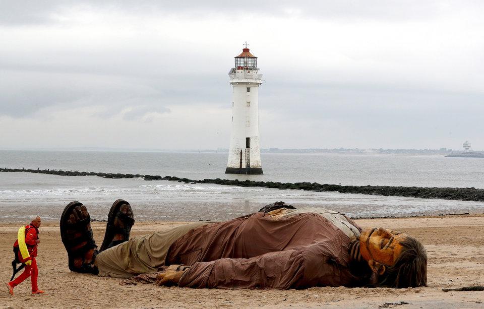 Спасатель проходит мимо одной из гигантских марионеток французского уличного театра Royal de Luxe, лежащей на пляже в Нью-Брайтоне, Великобритания.