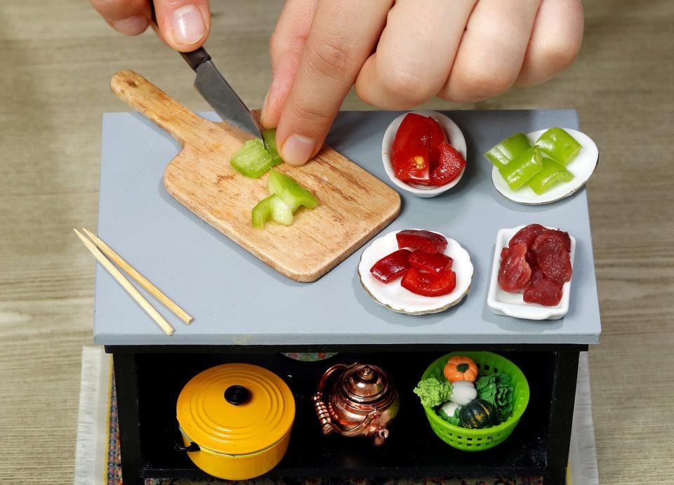урчу Челеноглу Айдын блистает навыками обращения крошечным ножом. Он готовит блюдо на своей миниатюрной кухне в Стамбуле, Турция.