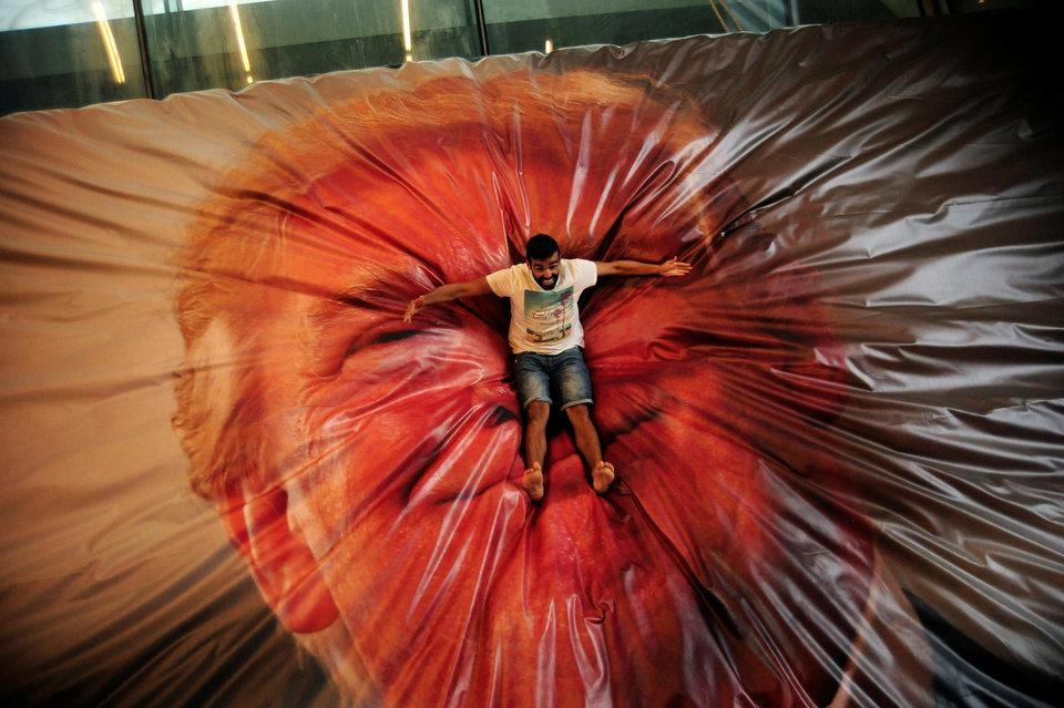 Парень приземлился на надувную конструкцию с изображением президента Дональда Трампа на международной выставке фотографии GetxoPhoto в Гечо, Испания.