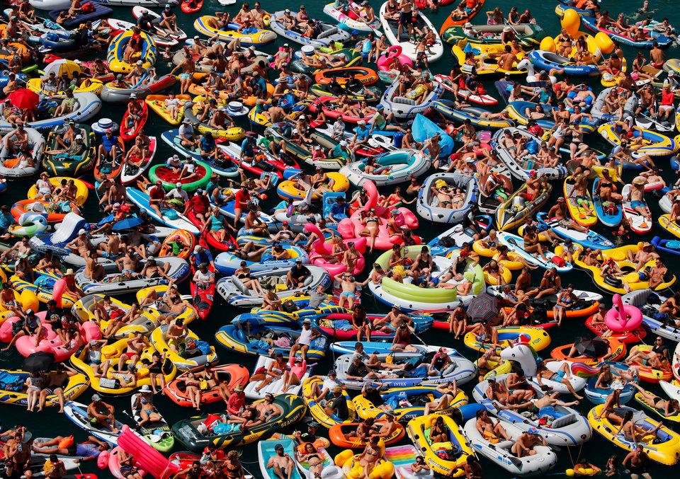 Люди на надувных лодках наслаждаются погодой на Фирвальдштетском (Люцернском) озере в Швейцарии.