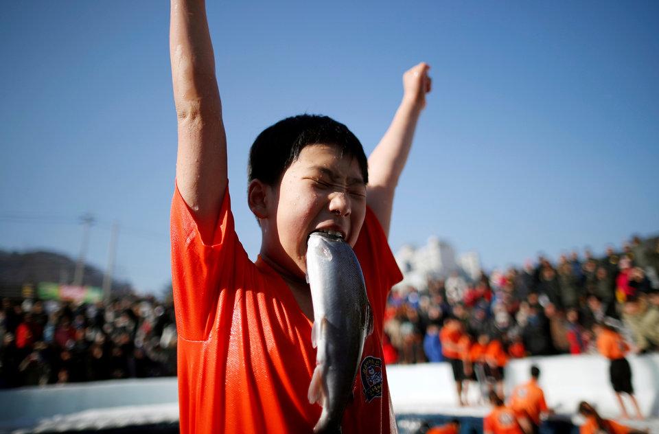 Мальчик радуется, поймав форель на фестивале в Хвачхоне, Южная Корея