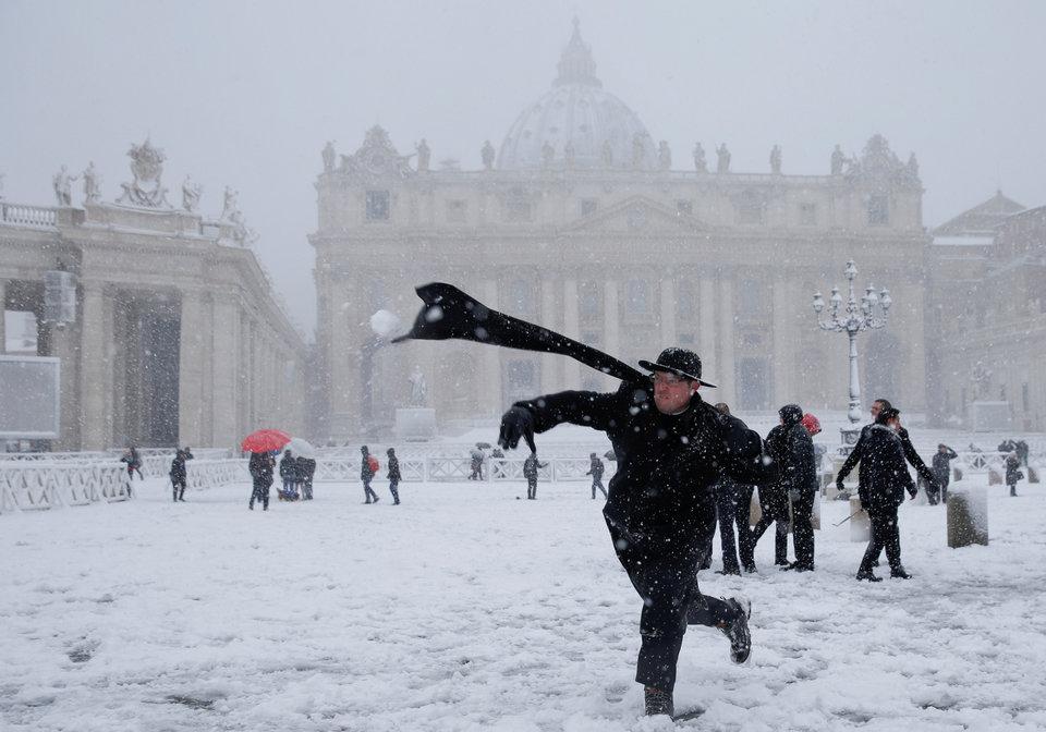 Молодой священник бросает снежок на площади Святого Петра в Ватикане во время обильного снегопада