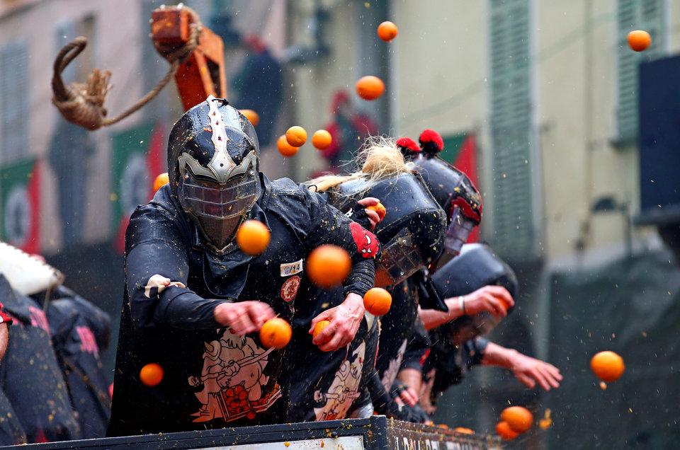 «Битва апельсинов» между членами соперничающих команд во время ежегодного карнавального сражения в Ивреа, Италия