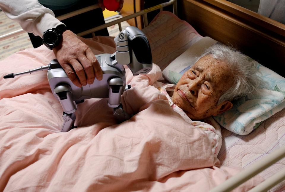 Йоичи Судзуки показывает собаку-робота AIBO своей прикованной к постели матери в своём доме в Такахаги, Япония