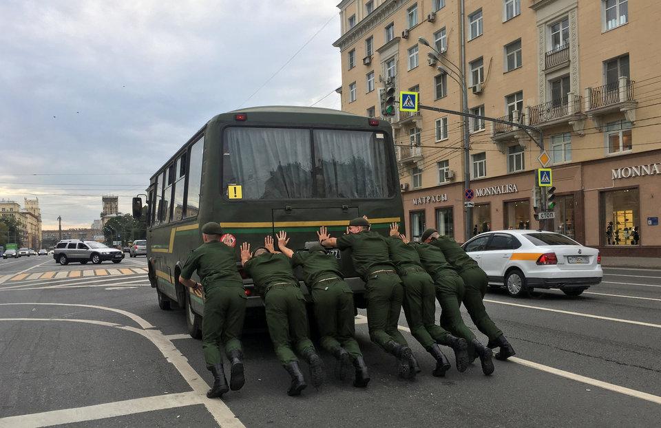 Семь российских военнослужащих толкают автобус по проспекту в Москве