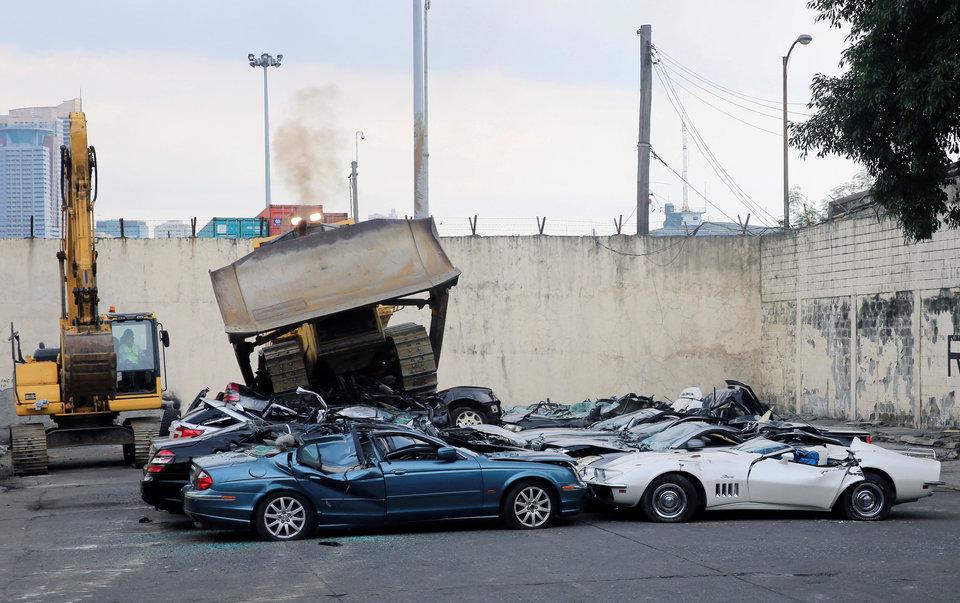 Бульдозер уничтожает контрабандные автомобили класса люкс