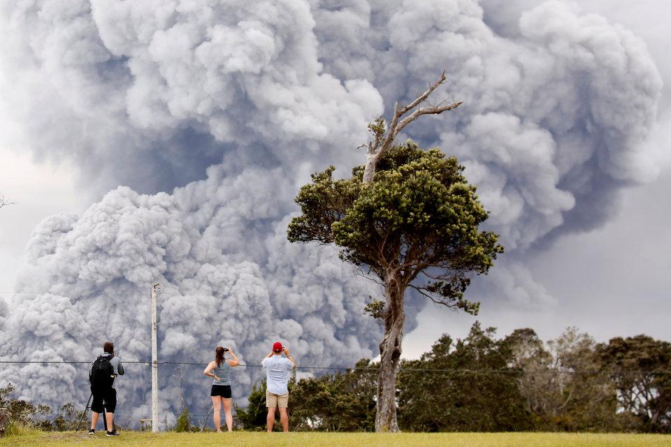 Вулкан Килауэа на острове Гавайи извергается в течение 35 лет. Люди наблюдают, как выбрасывается пепел из кратера Халемаумау.