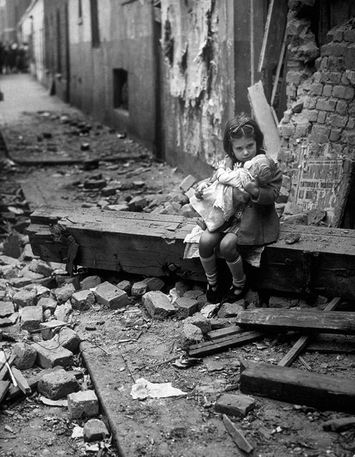 Девочка с куклой на руинах своего дома после бомбардировки Лондона в 1940 году.