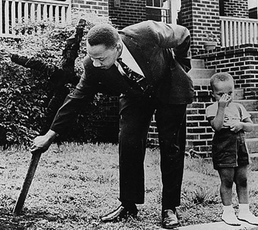 Мартин Лютер Кинг и его сын убирают сожженный крест с лужайки своего дома, 1960 год.