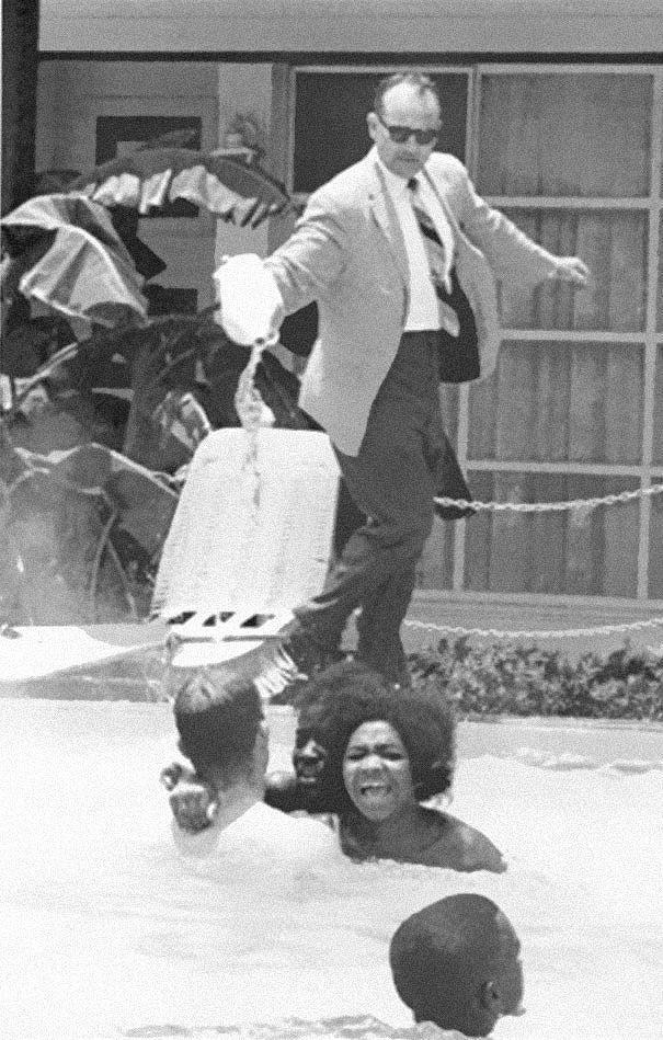 Владелец отеля выливает кислоту в бассейн, в котором плавают темнокожие, ок. 1964 года.